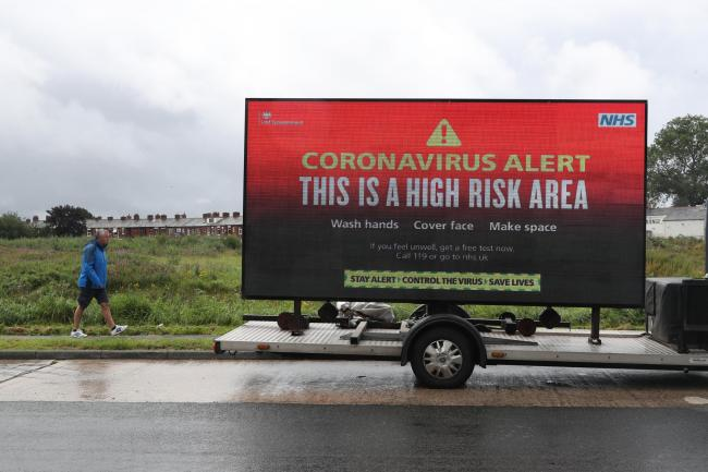 A mobile advertising vehicle displaying a coronavirus high risk area warning in Oldham, Greater Manchester, where residents have been told not to socialise with anyone outside their household and avoid using public transport unless it is essential. The lo