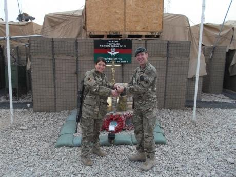 Brigadier Bob Bruce, Commander of 4th Mechanized Brigade, presenting Lance Corporal Amanda Schisano with her award