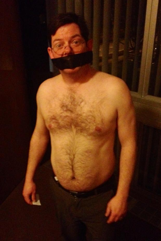 "Mark Sharp - in a black gag to ""highlight the lack of democracy"" in being made to remove his tshirt."