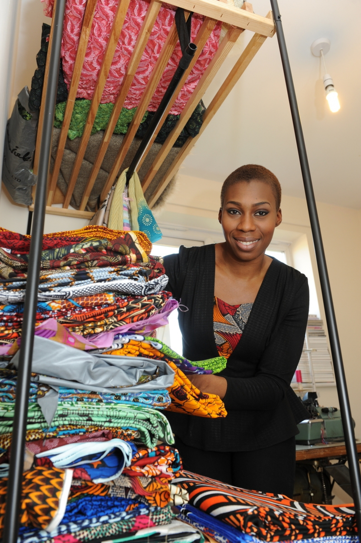 Chinelo Bally at work with a pile of fabrics at her home in Laindon