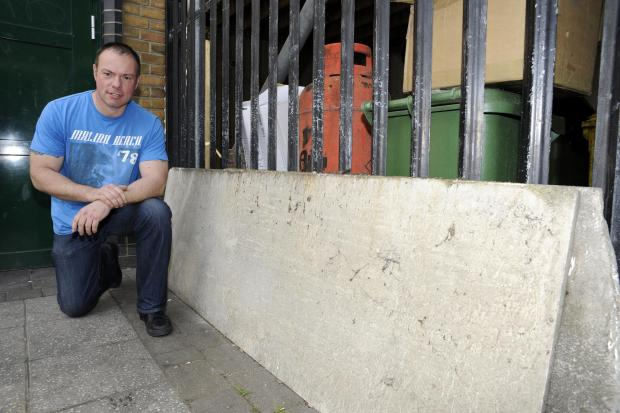 Risk to the public – construction worker Nigel Low with asbestos dumped outside the public toilets on Elm Road