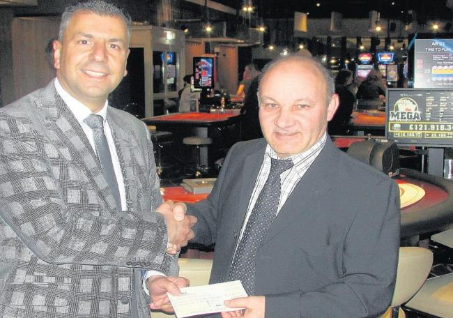 Cheque mate – the club's Andy Pieri, left, presents Goksel Selay with his winnings