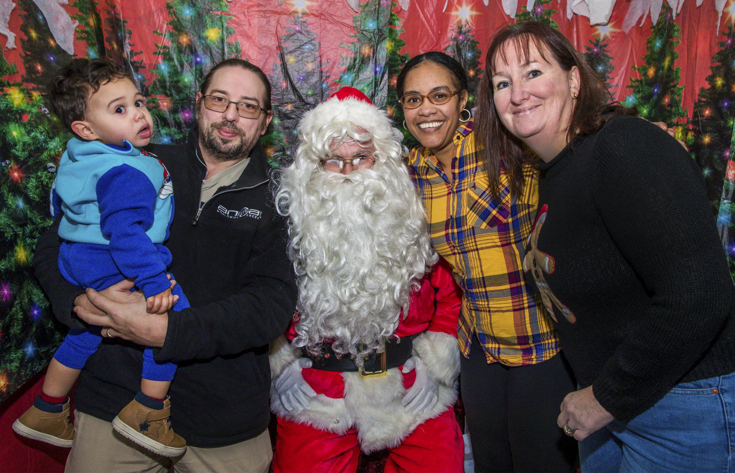 Santa visit - Ismail with dad Stuart, Santa, and mum Amira. Picture: Paul Starr