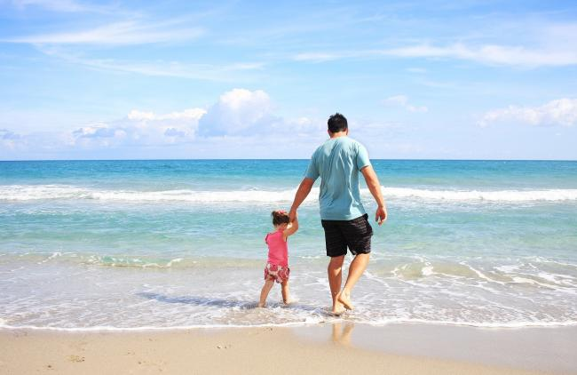 Stock image of a child and parent at the beach